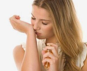 29032373-woman-smelling-perfume-on-her-wrist-300x245